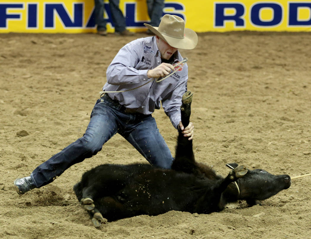 Cooper Martin of Alma, Kan. competes in Tie-down Roping in the eighth go-round of the Wrangler ...