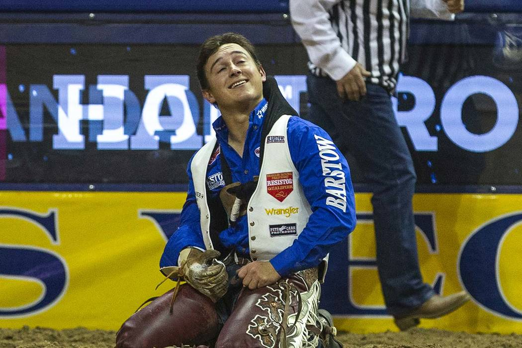 Clayton Biglow of Clements, Calif., looks up and smiles after he rides Ankle Biter to a first p ...