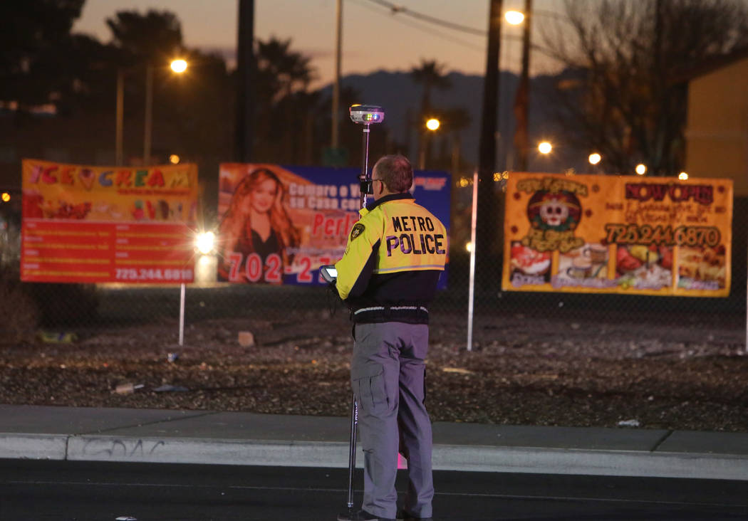 A Metropolitan Police Department officer investigates after two people died in a two-vehicle cr ...