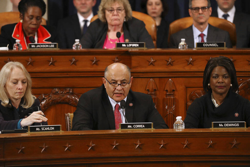 House Judiciary Committee member Rep. Luis Correa, D-Calif., center, votes for the first of two ...