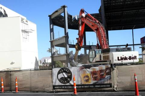 Crews from Las Vegas Demolition and Environmental Services demolish a structure behind the Hard ...