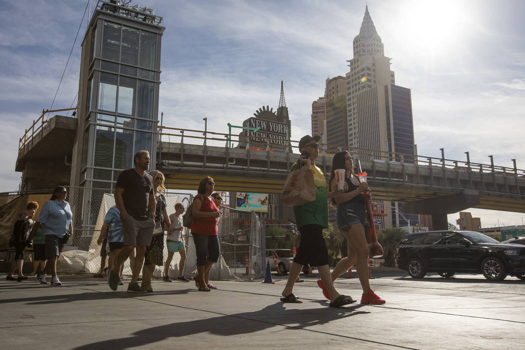 People walk along Las Vegas Boulevard in front of the pedestrian bridge being constructed to im ...