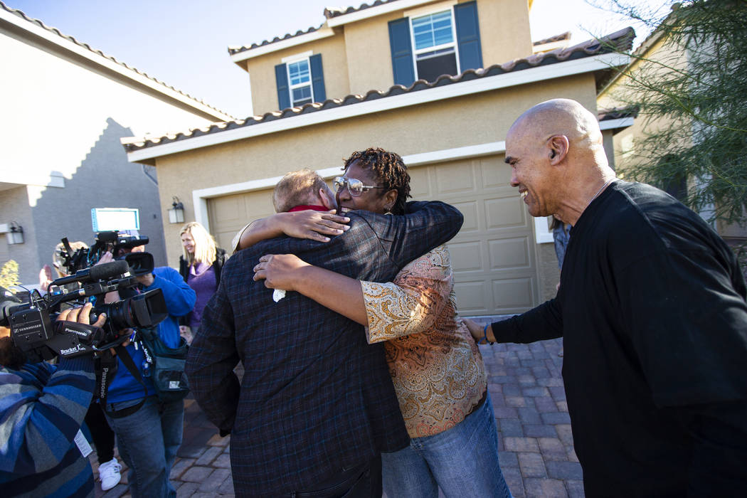 Lucille McKnight, center, hugs Walker Furniture CEO Larry Alterwitz while McKnight's partner, K ...