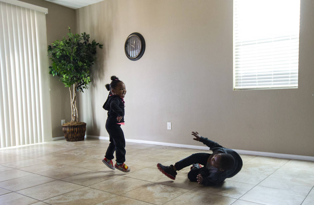 Christine Modica, 3, left, jumps around the open space in the living room with her brother, Noe ...