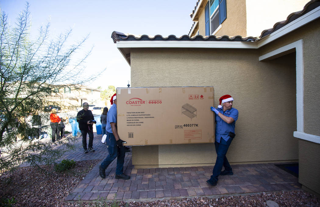 Employees from Walker Furniture deliver and set up a truckload of furnishings as part of their ...
