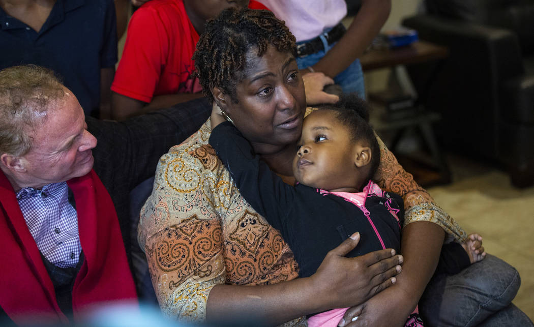 Lucille McKnight holds her great-niece Christine Modica, 3, while talking alongside Walker Furn ...