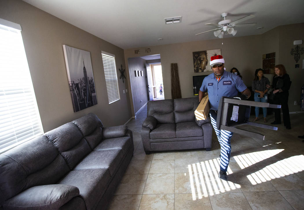 Walker Furniture employee Cole, who declined to give his last name, helps deliver and set up a ...