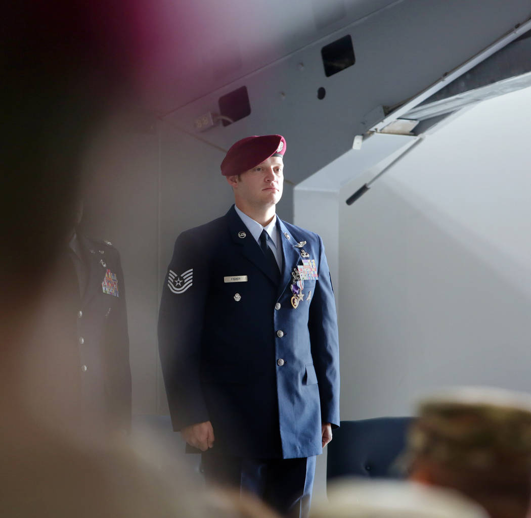 Technical Sgt. Gavin Fisher stands for applause after receiving the Purple Heart and Silver Sta ...