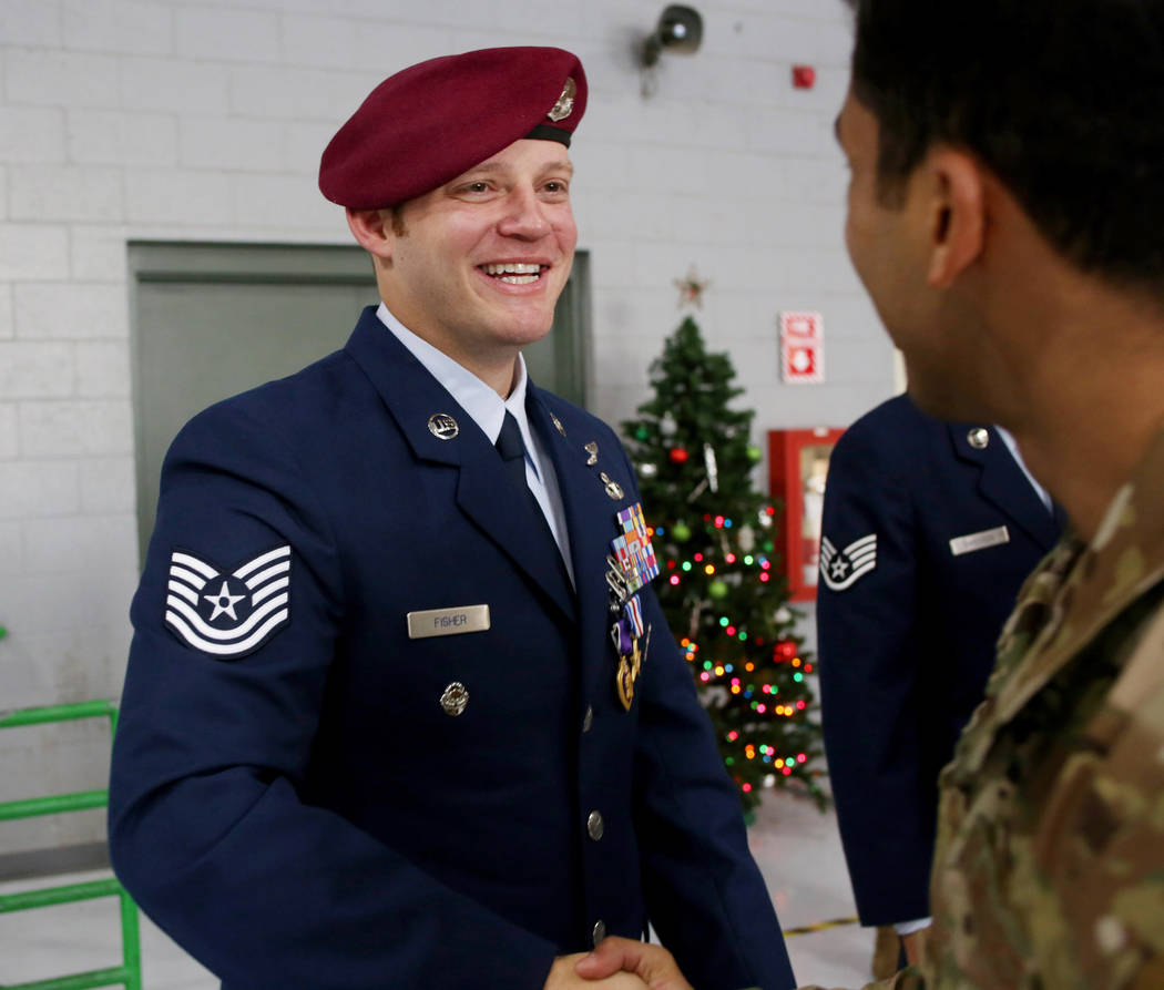 Technical Sgt. Gavin Fisher shakes the hand of a member of the military after receiving the Pur ...