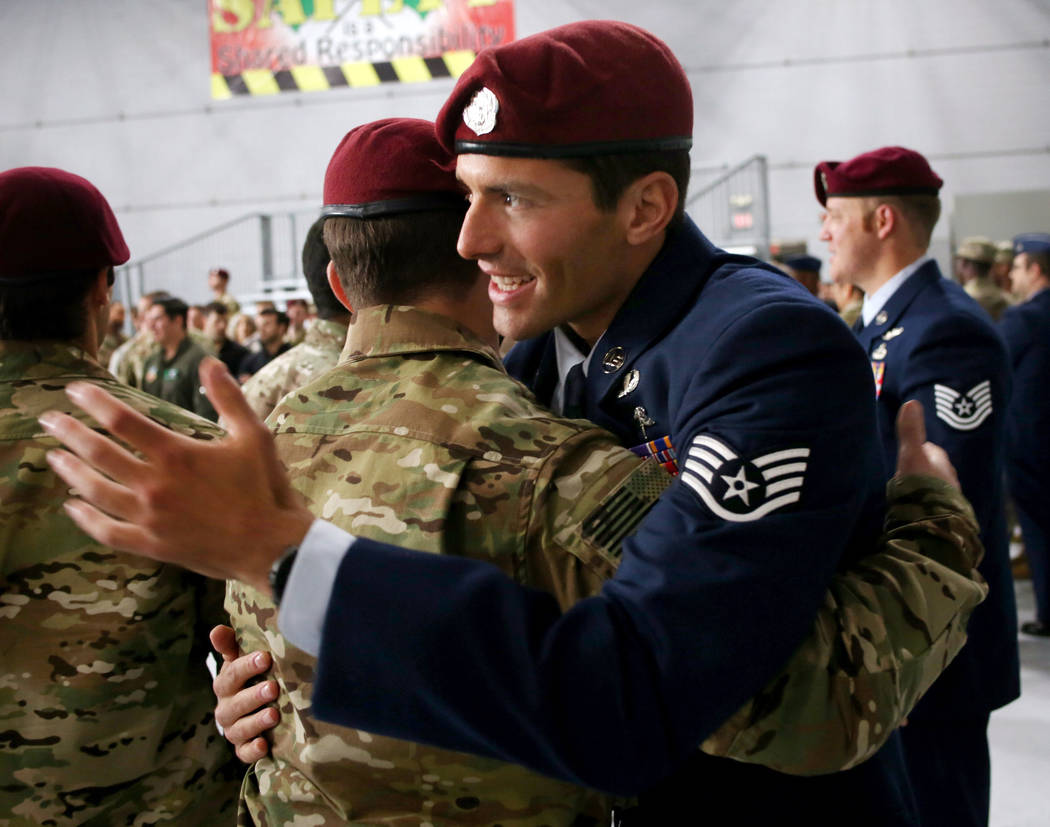 Staff Sgt. Daniel Swensen, right, hugs a member of the military after a ceremony awarding the S ...