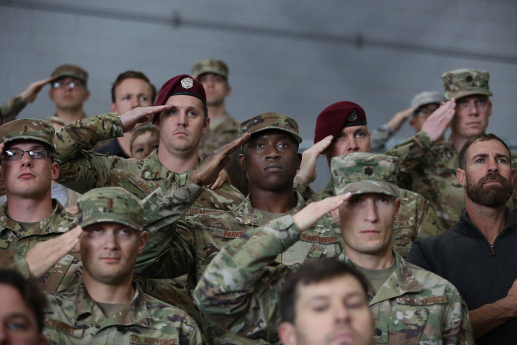 Members of the military salute during a ceremony awarding the Purple Heart and Silver Star Meda ...
