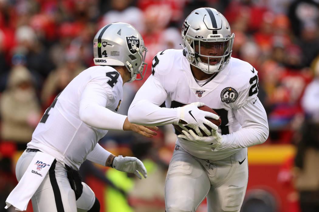 Oakland Raiders quarterback Derek Carr (4) hands off the football to running back Josh Jacobs ( ...