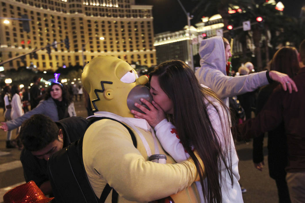 A reveler steals a kiss from Homer Simpson during the New Year's Eve celebration on the Las Veg ...