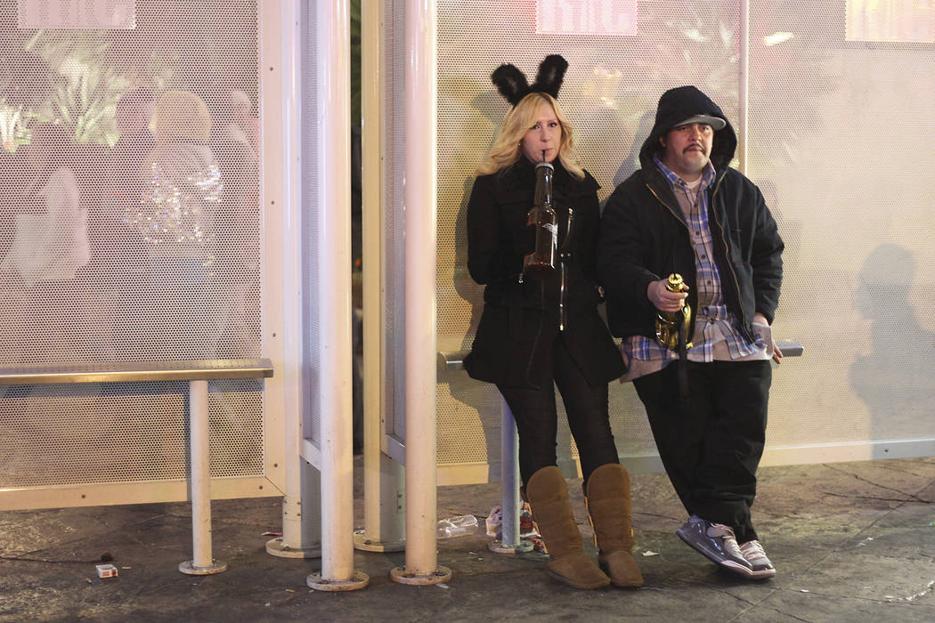 Two partyers take a break from the action during the New Year's Eve celebration on the Las Vega ...