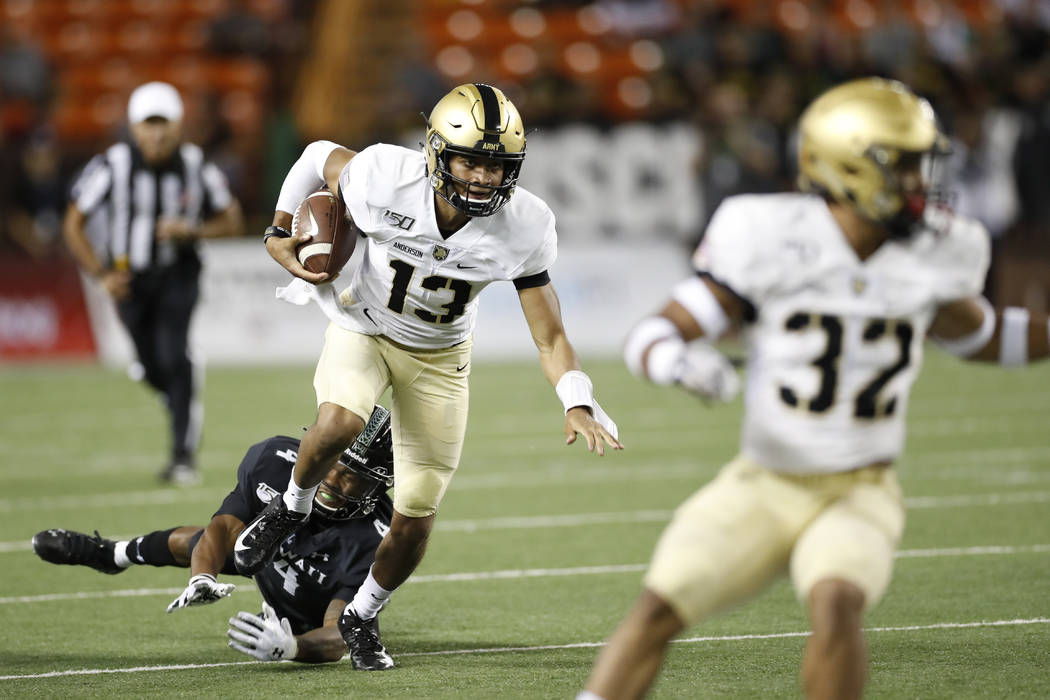 Army quarterback Christian Anderson (13) gets away from Hawaii defensive back Rojesterman Farri ...