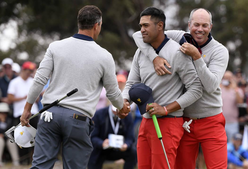 International team player Adam Scott of Australia, left, shakes hands with U.S. team player Ton ...