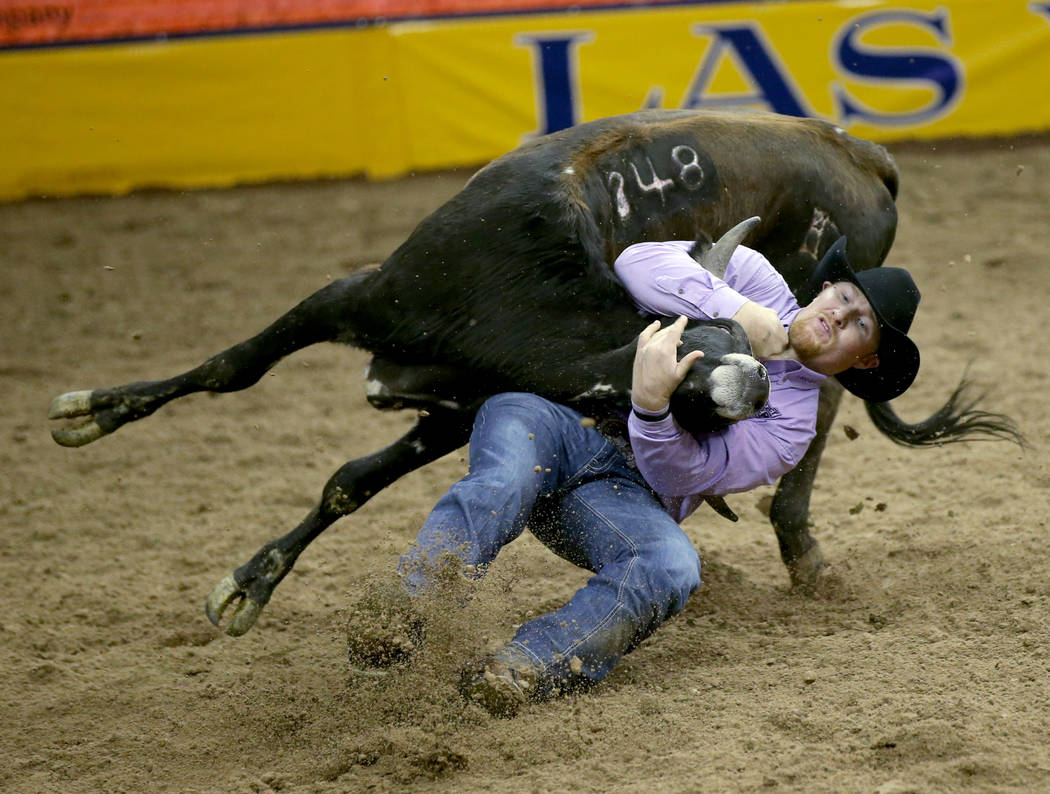 Stetson Jorgensen of Blackfoot, Idaho competes in Steer Wrestling during the ninth go-around of ...