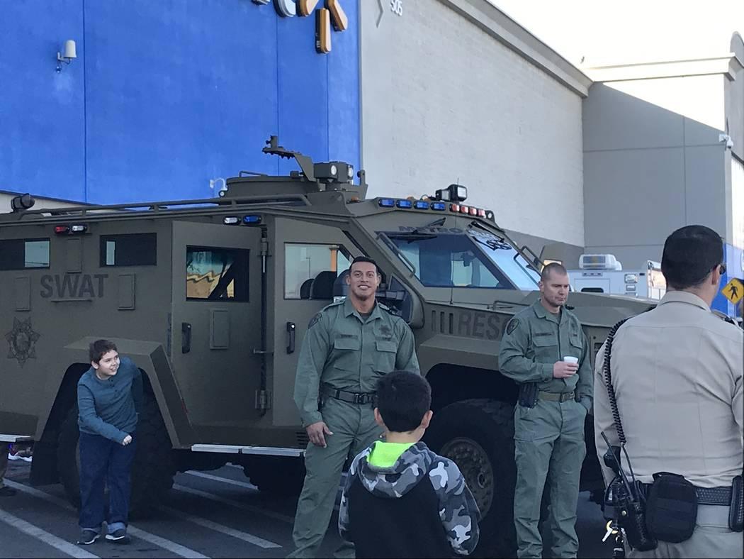 "The Metropolitan Police Department's SWAT unit watch the festivities during a ""Santa Cops"" even ..."