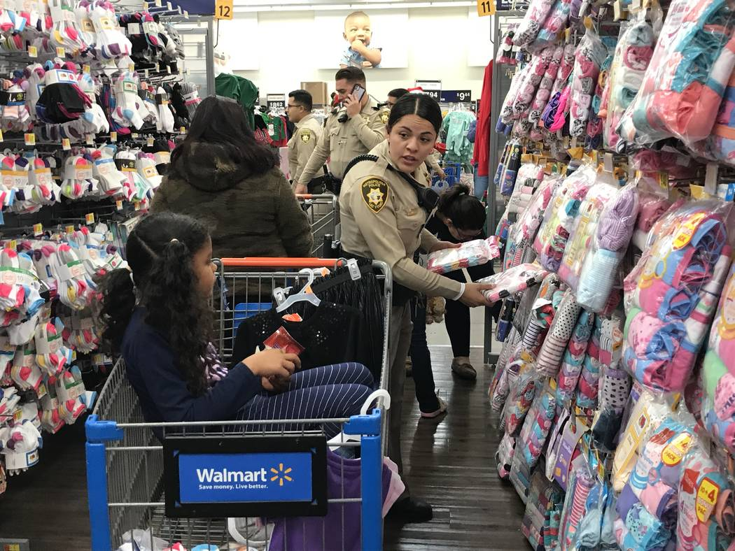 Metropolitan Police Department officer Alexis Hodler shops with 6-year-old Cathalina Correa dur ...