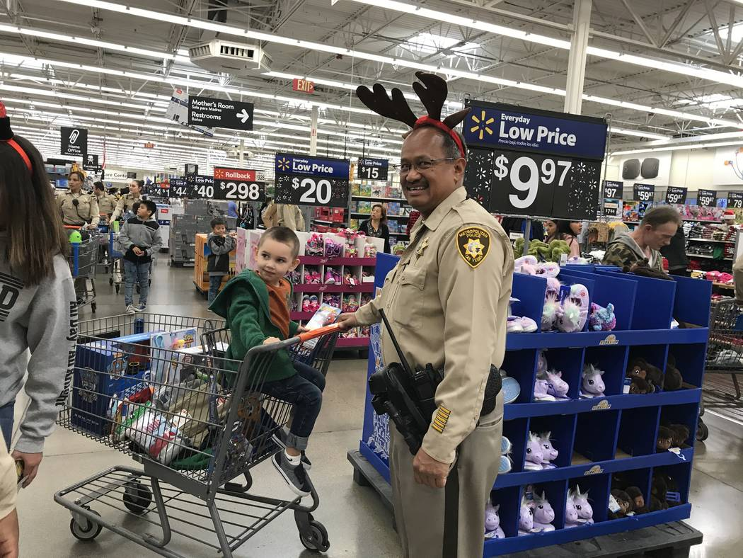 Metropolitan Police Department officer Ed Serrano pushes 3-year-old Justus in a shopping cart d ...