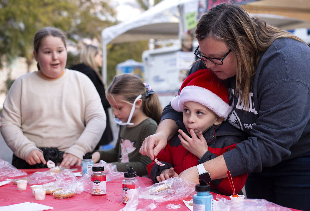 Travis Williams, 6, sneaks a bite of frosting as he decorates a cookie with the help of his mot ...