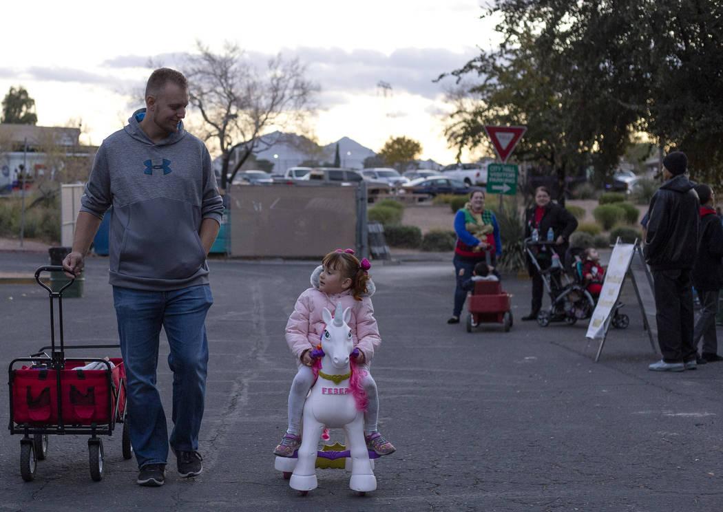 Corey Conrad, left, walks into WinterFest as his daughter Dalya, 4, right, rides a unicorn into ...
