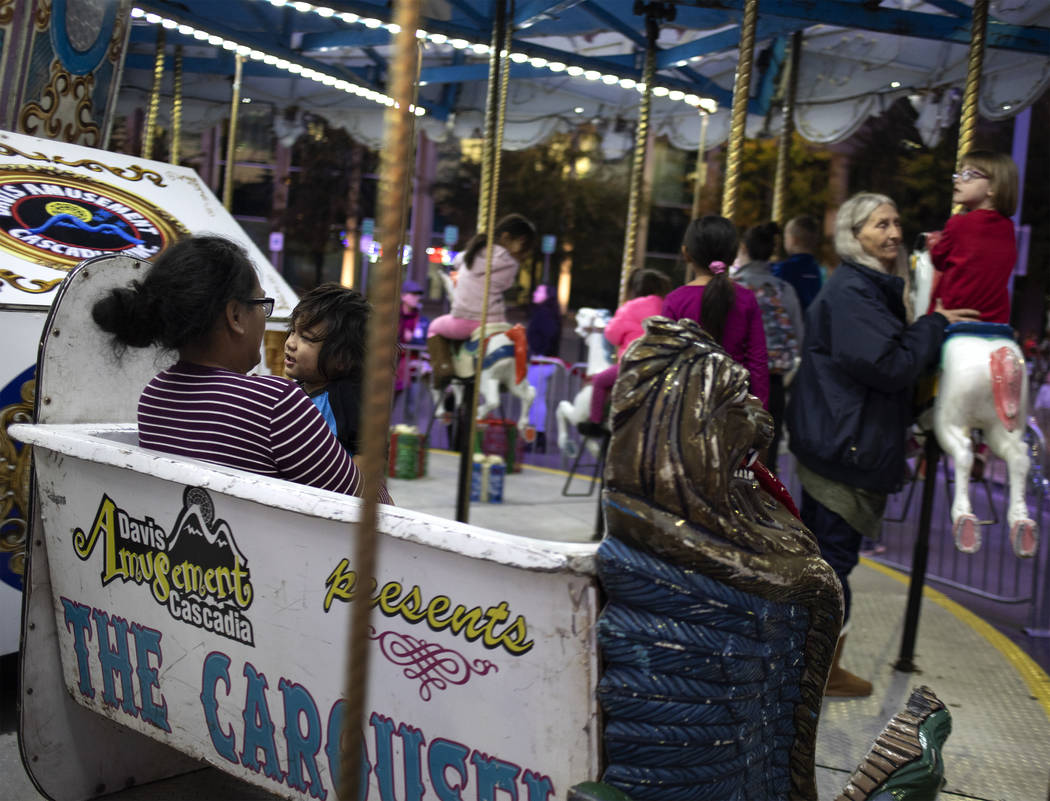 Pearl Viliamu, left, holds her son, Daxson, 2, on the carousel at Henderson's annual WinterFest ...