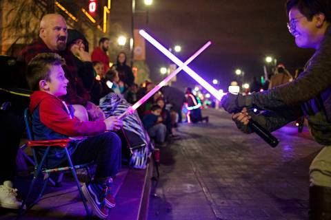 Logan Rush, 5, left, crosses light sabers with a member of Las Vegas Star Wars Clubs during the ...