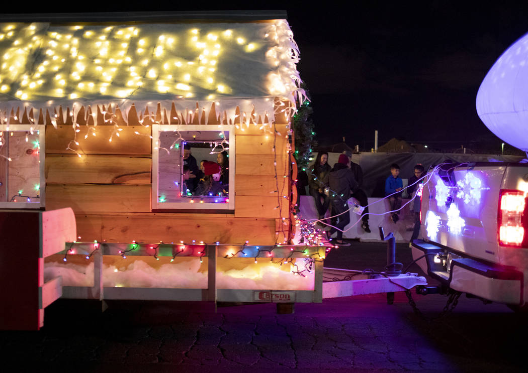 Rooftop Realty's float passes by as spectators sit along the road blocks at Henderson's annual ...