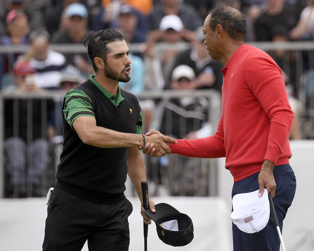 U.S. team player and captain Tiger Woods, right, shakes hands with International team player Ab ...
