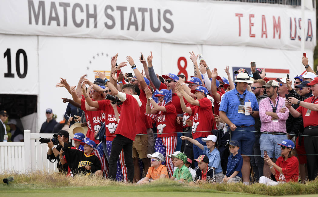Fans of the U.S. team celebrate at the 16th hole after U.S. team player and captain Tiger Woods ...