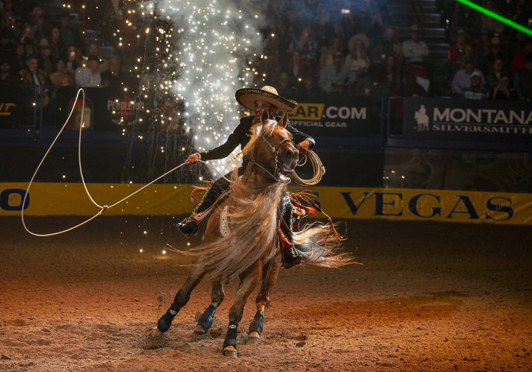 A trick roper performs as part of the opening act during the tenth go round of the Wrangler Nat ...