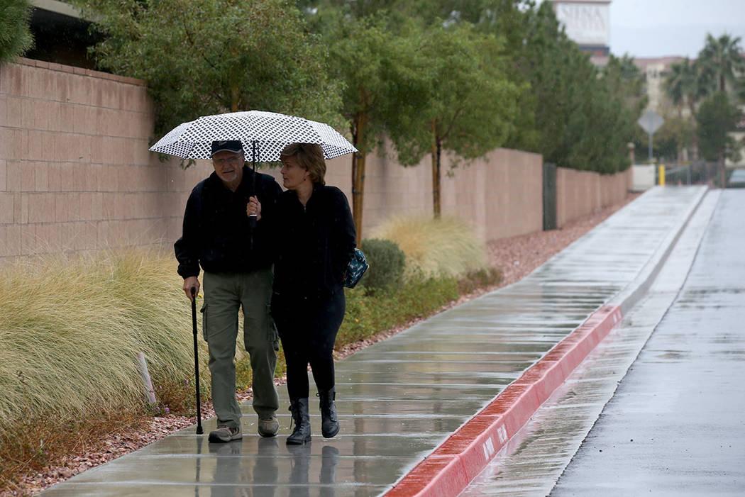 Ross and Angela Bracale share an umbrella under light rain near Russel Road and Boulder Highway ...