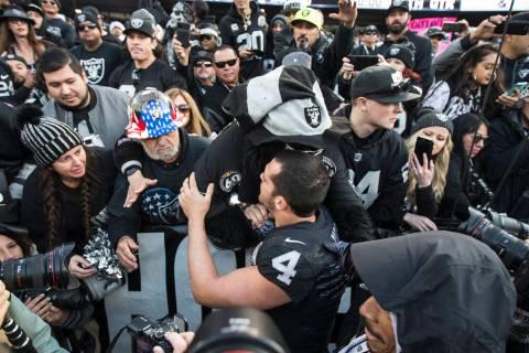 """Oakland Raiders quarterback Derek Carr (4) hugs fans in the """"Black Hole"""" after Oaklan ..."""