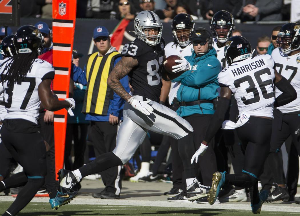 Oakland Raiders tight end Darren Waller (83) makes a big catch and run past Jacksonville Jaguar ...