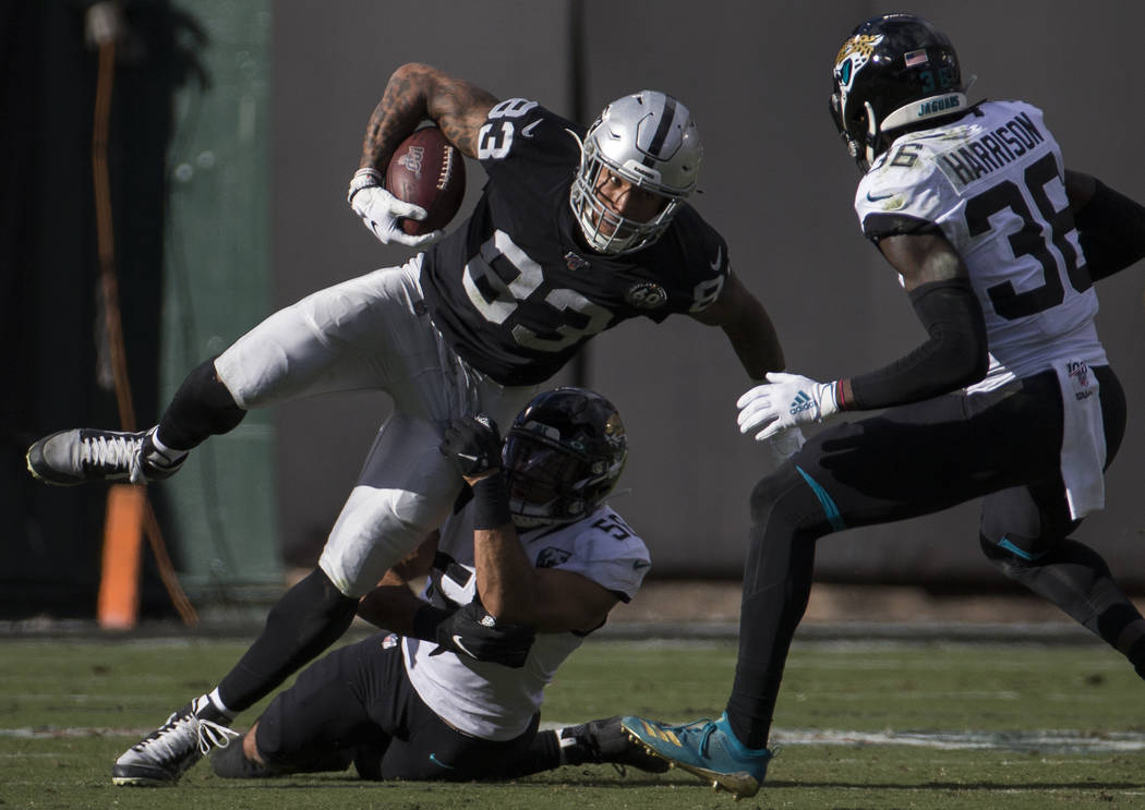 Oakland Raiders tight end Darren Waller (83) fights for extra yardage with Jacksonville Jaguars ...