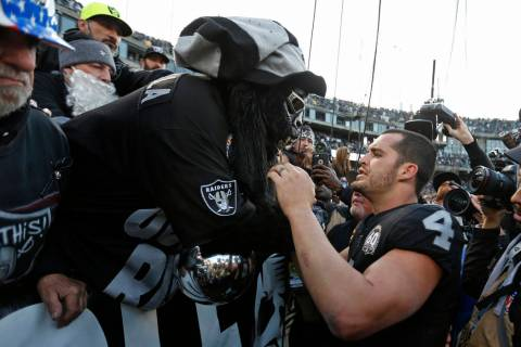"Oakland Raiders quarterback Derek Carr (4) is met by Gorilla Nilla in ""The Black Hole&quot ..."