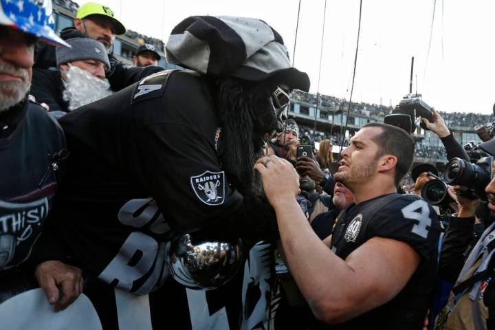 "Oakland Raiders quarterback Derek Carr (4) is met by Gorilla Nilla in ""The Black Hole&quot ..."
