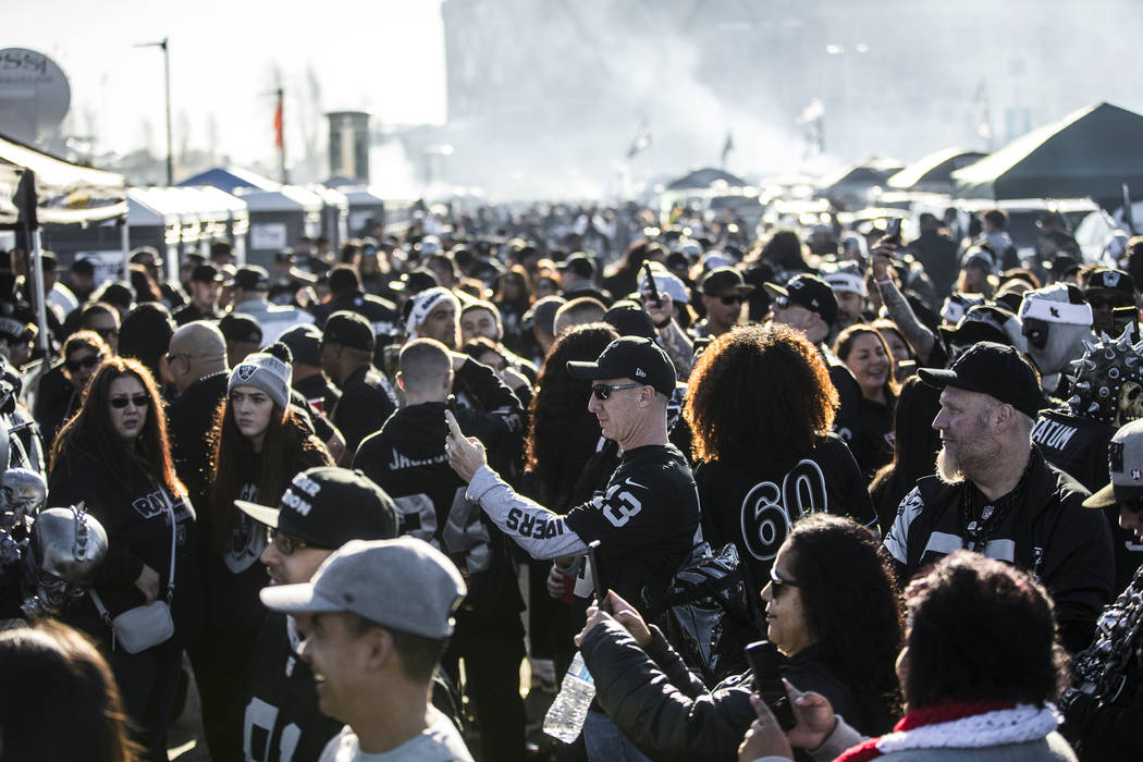 Fans tailgate outside the Oakland Coliseum before the start of an NFL football game between the ...