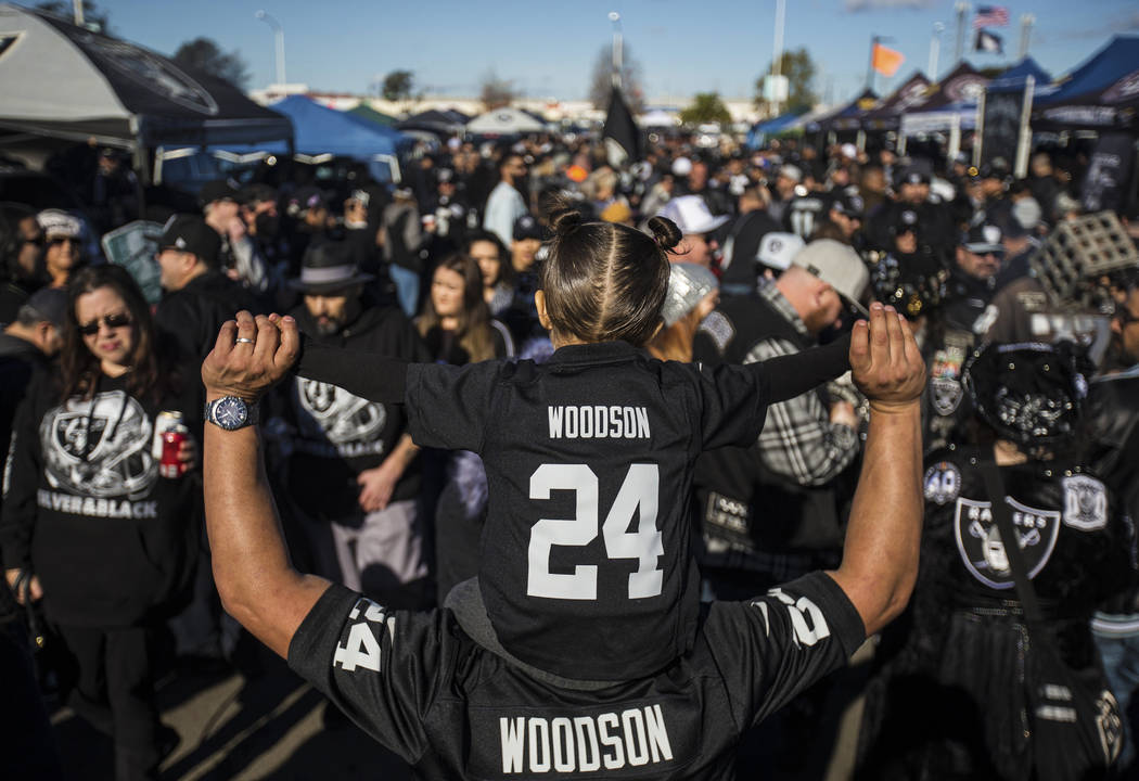 Roman Arroyo holds his daughter Emma, 3, at a tailgate outside the Oakland Coliseum before the ...