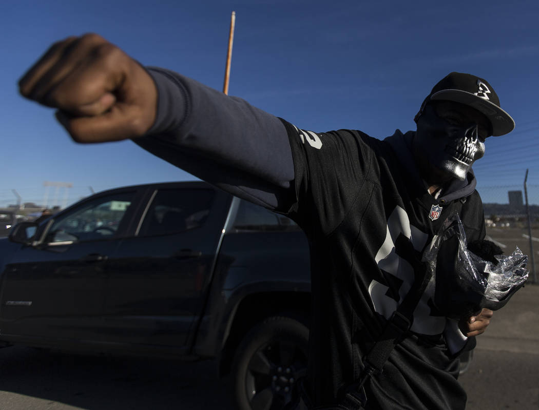 Vendors sell masks to passing cars outside the Oakland Coliseum before the start of an NFL foot ...