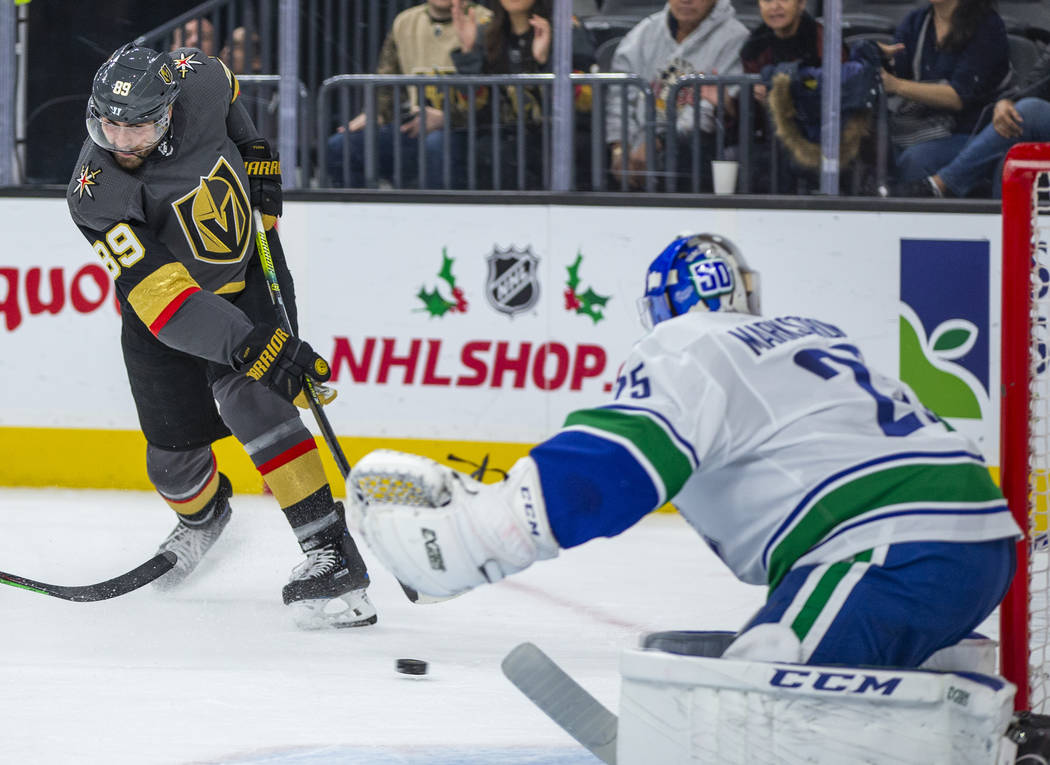 Vegas Golden Knights right wing Alex Tuch (89) shoots towards the net defended by Vancouver Can ...