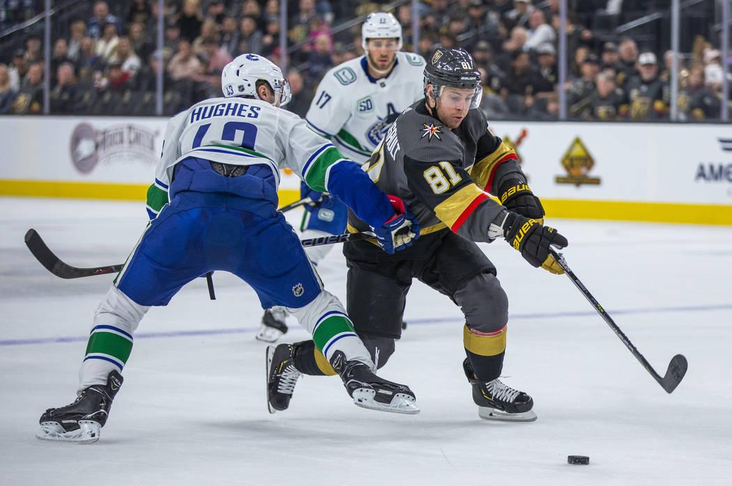 Vegas Golden Knights center Jonathan Marchessault (81) squeezes past Vancouver Canucks defensem ...