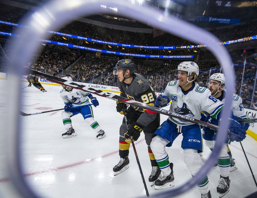 Vegas Golden Knights left wing Tomas Nosek (92, center) battles for position with Vancouver Can ...