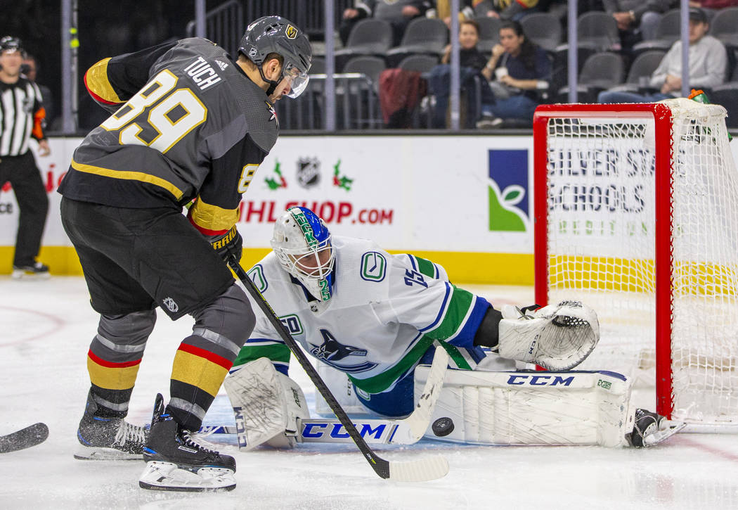 Vegas Golden Knights right wing Alex Tuch (89, left) takes a shot at the net on Vancouver Canuc ...