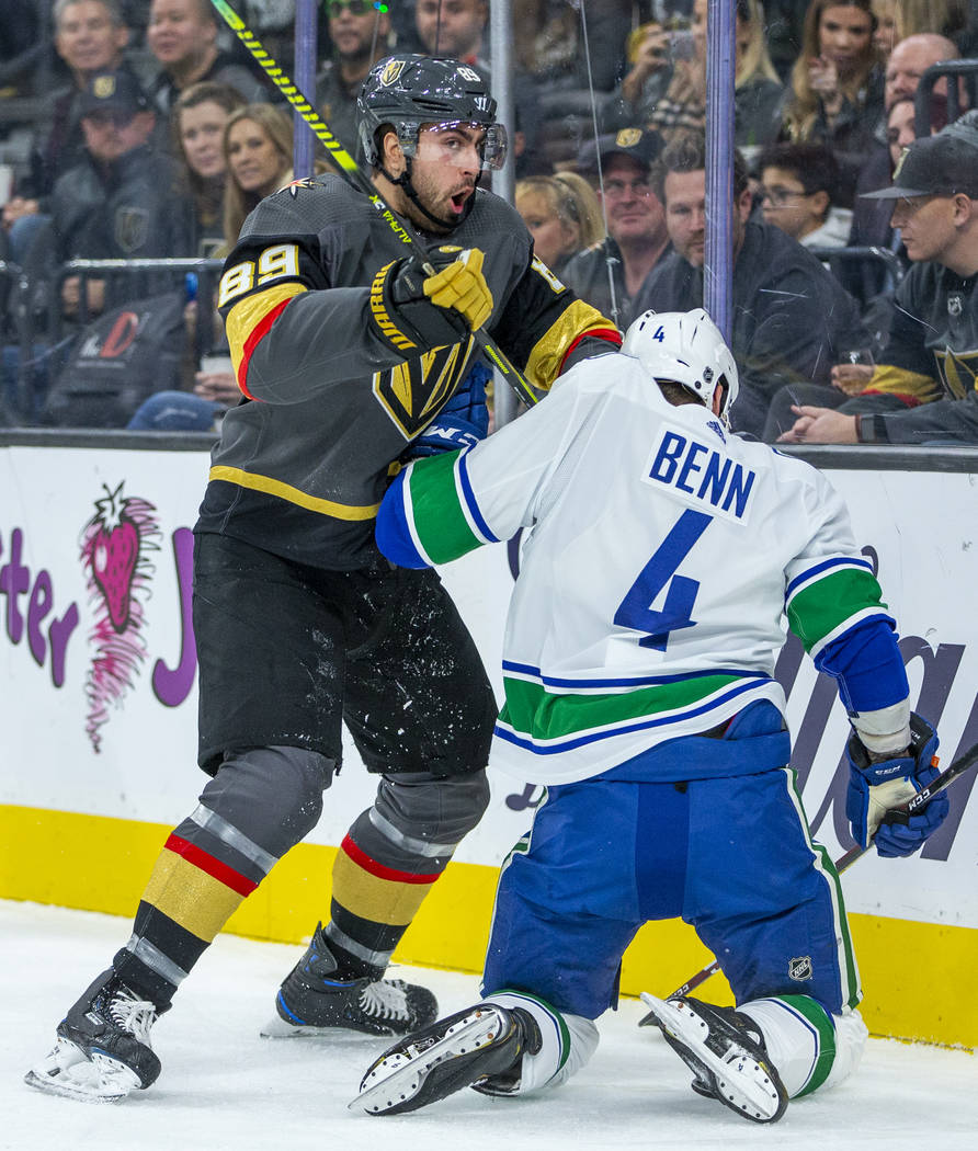 Vegas Golden Knights right wing Alex Tuch (89, left) tangles with Vancouver Canucks defenseman ...