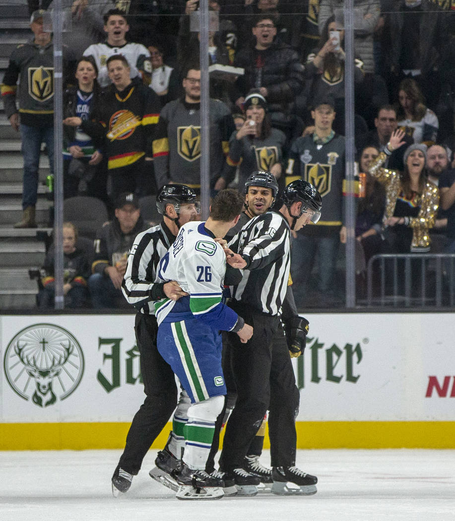 Vancouver Canucks left wing Antoine Roussel (26, front) and Vegas Golden Knights right wing Rya ...