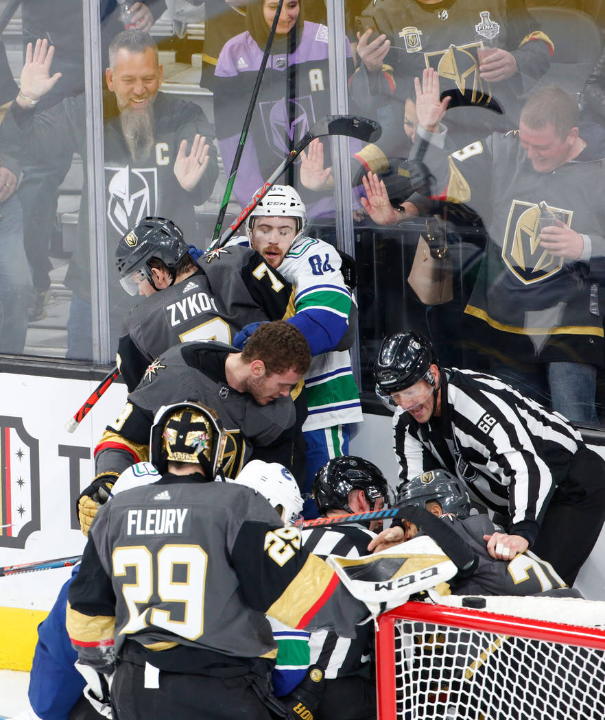Vegas Golden Knights left wing Valentin Zykov (7), left top, fights with Vancouver Canucks cent ...