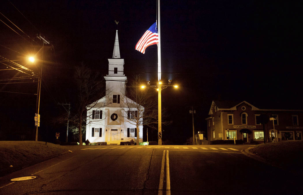 FILE - In this Dec. 15, 2012 file photo, a U.S. flag flies at half-staff on Main Street in Newt ...