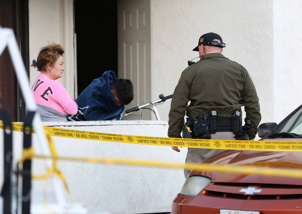 A Metropolitan Police Department officer talks to residents at the 2300 block of Exeter Drive, ...